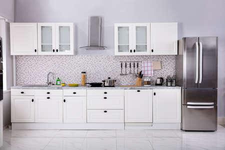 Innenraum der modernen weißen sauberen Küche mit Mikrowelle und Kühlschrank