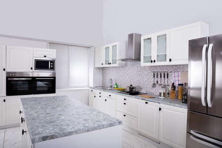 Interieur van moderne witte schone keuken met magnetron en koelkast