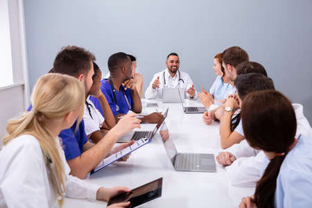 Positive Young Specialists With Stethoscope Having Discussion Of Research Work In Conference Room Reklamní fotografie