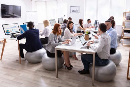 Group Of Multi-ethnic Businesspeople Sitting On Fitness Ball Having Discussing While Working In Office