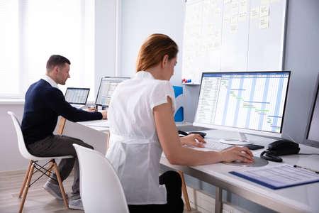Businesswoman Analyzing Gantt Chart On Desktop In Office Sitting Behind Male Colleague