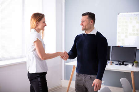 Side View Of Happy Businessman Shaking Hands With His Partner At Office Stock Photo