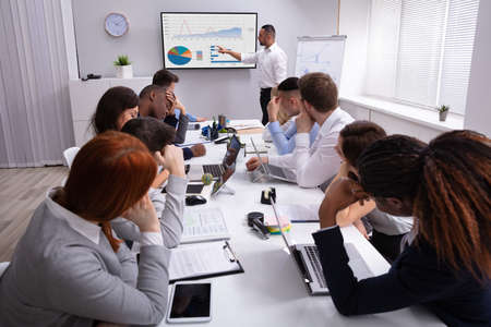 Group Of Business Executives Tired Of Long Meeting In Office
