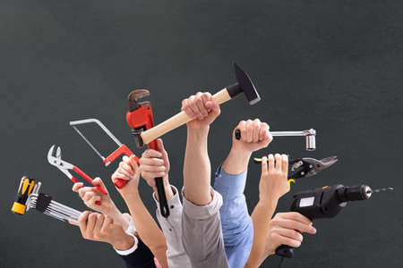 Close-up Of Peoples Hand Holding Carpentry Tools Against Black Background