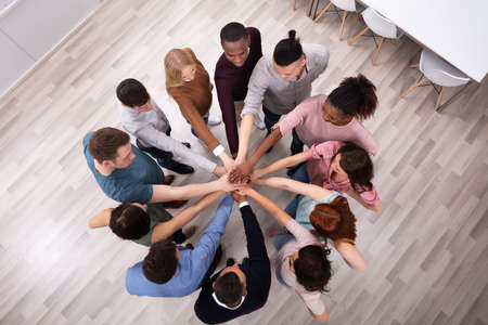 Vista de ángulo alto de amigo multirracial mano de apilamiento juntos Foto de archivo
