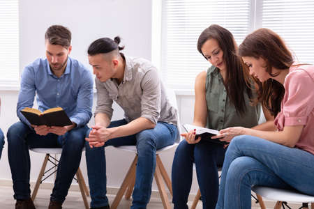 Group Of Friend Sitting Together On Chair Reading Bible