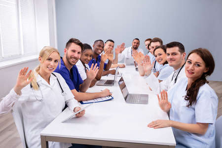 Group Of Happy Doctors Waving Their Hands At Medical Conference