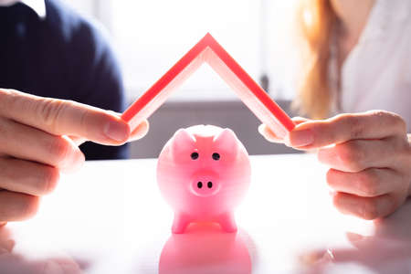 Human Hand Protecting Pink Piggybank With Red Roof Over White Desk Stock Photo