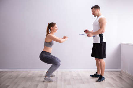 Side View Of Young Sporty Woman Doing Deep Squat Exercise In Front Of Gym Trainer