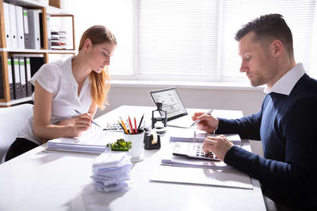 Side View Of Businessman And Businesswoman Calculating Invoice With Calculator Over White Desk In Office