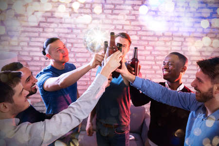 High Angle View Of Multiracial Friends  Clenching Beer Bottles At Disco Bar