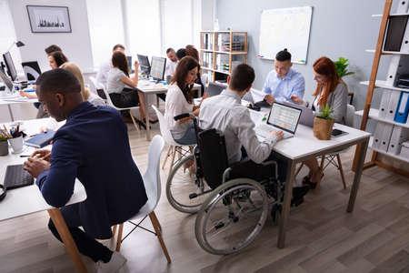 Vista laterale di un imprenditore disabile seduto su sedia a rotelle utilizzando laptop lavorando in Office