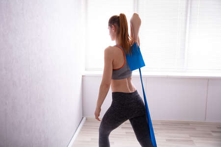 Young Woman Stretching With Yoga Belt While Doing Exercise At Home