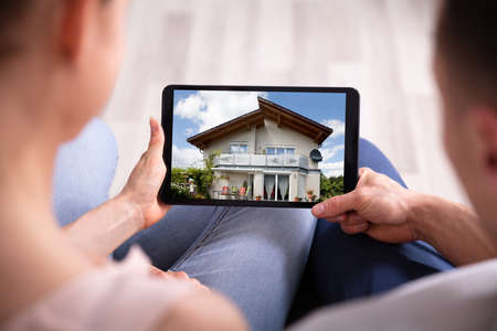 Close-up Of A Couple Looking At New House On Tablet
