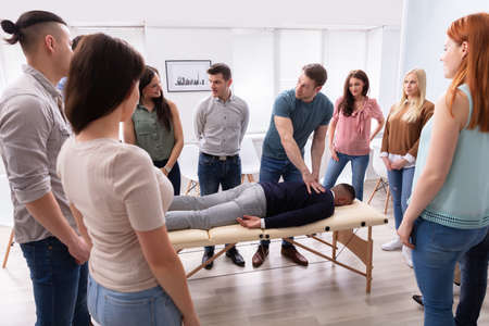 Instructor masculino enseñando técnica de masaje a un grupo de personas multiétnicas
