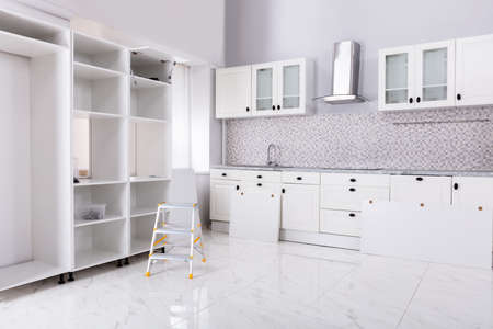 Installation Of Wooden Cabinets In The White Clean Modular Kitchen