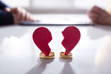 Close-up Of Broken Red Heart And Weeding Rings Over White Desk