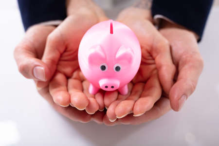 Elevated View Of Pink Piggybank On Palm Of Couples Hand Over White Desk Stock Photo