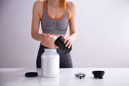 Young Sporty Woman Preparing Protein Shake Before Workout On Desk Stock Photo