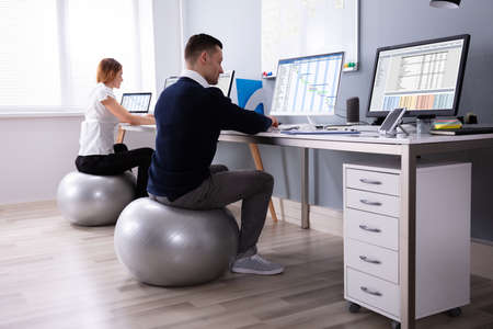Two Businesspeople Working On Computer In Office Sitting On Fitness Ball