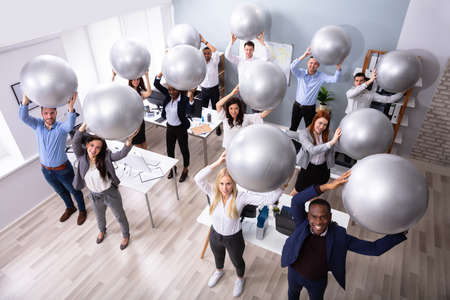 Happy Group Of Businesspeople Stretching Their Arms Using Fitness Ball In Office Stock Photo