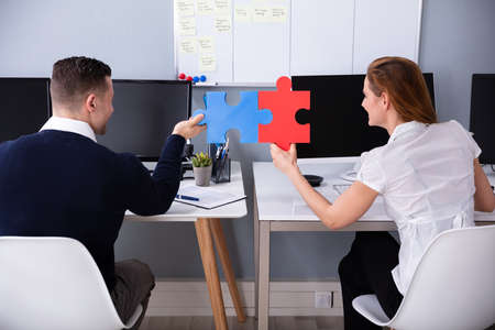 Rear View Of Two Businesspeople Joining Red And Blue Colored Jigsaw Pieces In Office