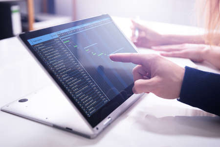 Close-up Businessman's Hand Showing Gantt Chart On Laptop Screen Over White Desk In Office
