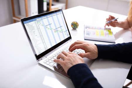 Businessman's Hands Working On Gantt Chart On Laptop Over Desk At Workplace Stock fotó