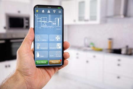 Primo piano della mano dell'uomo che tiene il cellulare con la funzione dell'icona di controllo della casa intelligente con sfondo della cucina Kitchen