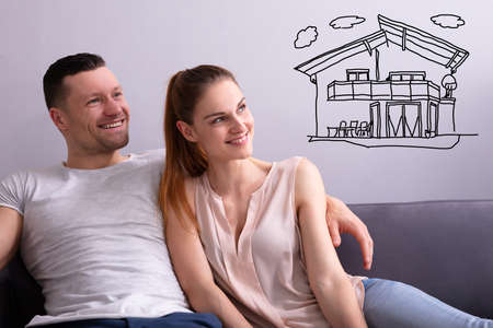 Happy Couple Dreaming Of Having Future Home While Sitting On Sofa