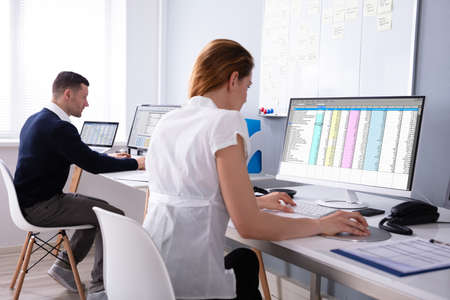 Side View Of Male And Female Businesspeople Sitting In Office Examining Report On Computer Stock fotó