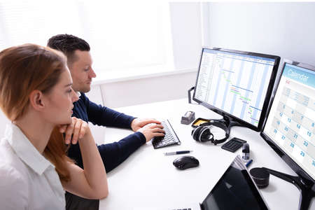 Young Businesspeople Analyzing Gantt Chart And Calendar On Computer In Office
