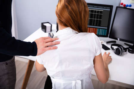 Businessman's Sexually Harassing Female Colleague By Touching Her Shoulder Stock Photo - 126998570