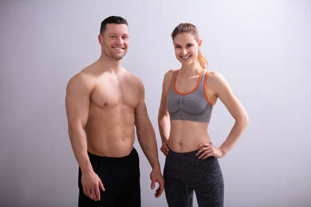 Photo Of Smiling Sporty Couple Against Gray Background
