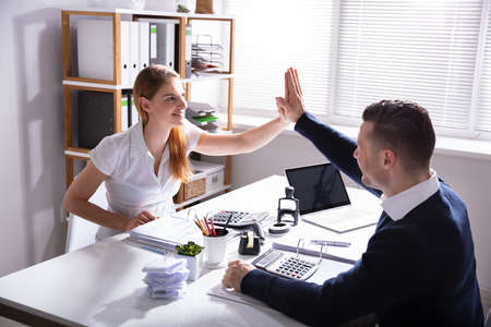 Happy Businessman Giving High Five To His Colleague In Office Banco de Imagens