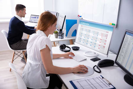 Businesswoman Looking At Calendar On Desktop Computer With Colleague Behind In Office
