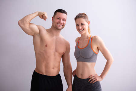 Portrait Of Smiling Young Couple Showing Muscles 版權商用圖片