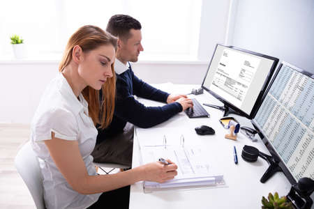 Male And Female Auditors Working On Computer With Invoice At Workplace