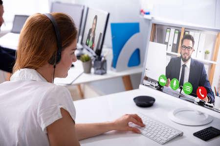 Close-up de la empresaria videoconferencia con su colega masculino en la computadora en el lugar de trabajo