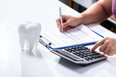 Close-up Of White Tooth Over Desk In Front Of Man Calculating Bill With Calculator