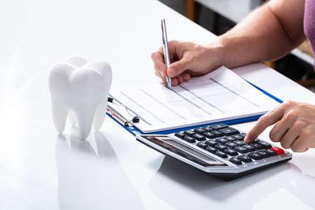 Close-up de diente blanco sobre el escritorio delante del hombre calculando la factura con la calculadora Foto de archivo