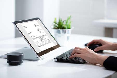Close-up van de handen van de zakenvrouw bezig met factuur op laptop op kantoor Stockfoto
