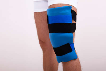 Close-up Of A Man With Blue Knee Ice Pack Against White Backdrop