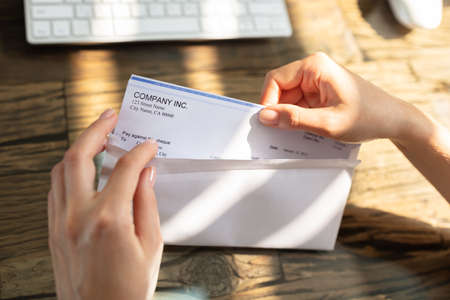 Close-up Of A Businesspersons Hand Opening Envelope With Paycheck Over Wooden Desk