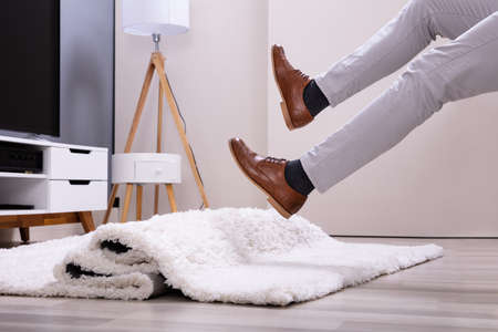 Low Section Of Man Legs Stumbling With A Carpet In The Living Room At Home Imagens