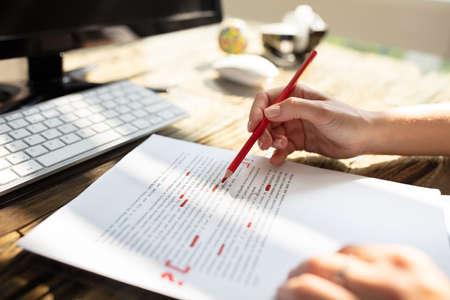 Close-up van iemands hand die fout markeert met rode markering op document