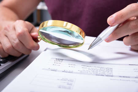 Close-up Of A Accountant's Hand Holding Magnifying Glass Checking Bill At Workplace