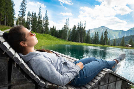 Woman Relaxing In Sun Lounger Near Lake In Mountains