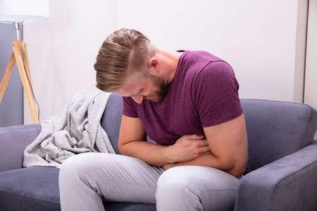Hombre joven que sufre de dolor de estómago sentado en el sofá en casa