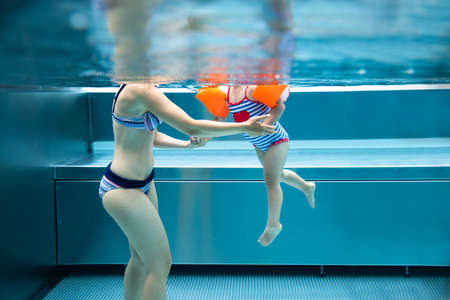 Above Below Water Photo Of Mother And Child Girl Swimming In Pool In Mountains Reklamní fotografie